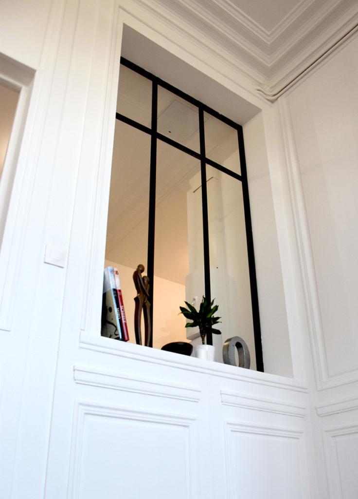 Verrière lumineuse dans un appartement rénové clair et classique
